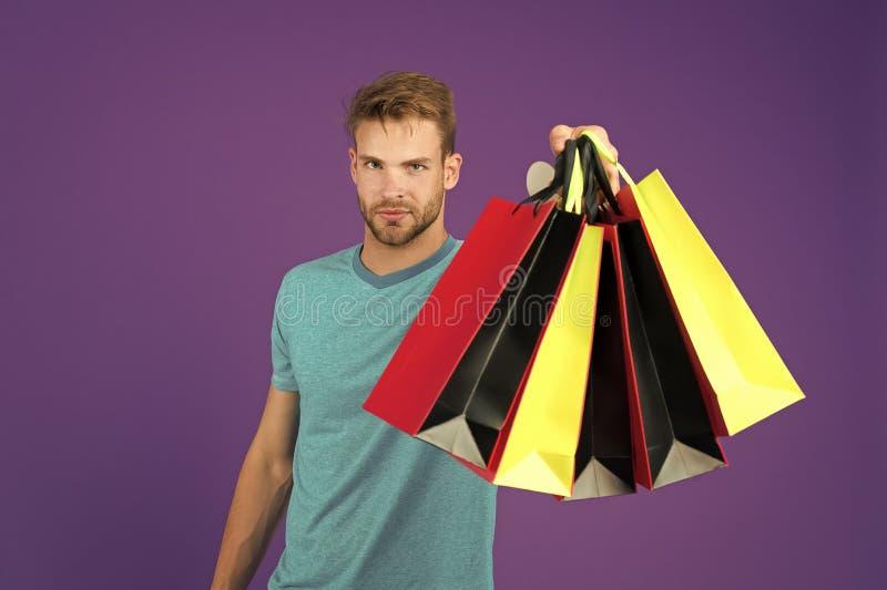 Shopping eller försäljning och cyber måndag Man med shoppingpåsar på violett bakgrund Macho med färgrika pappers- påsar Mode royaltyfri foto