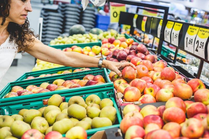 Shopping för den unga kvinnan bär frukt i supermarket royaltyfria bilder