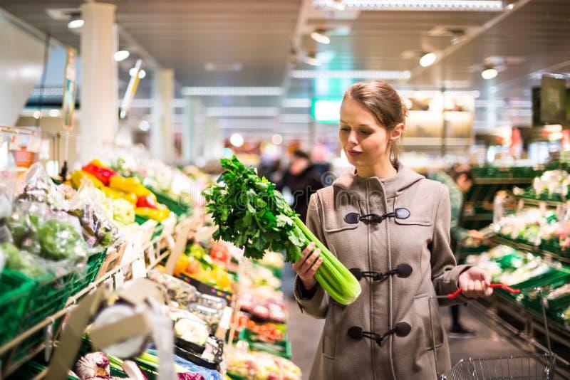 Shopping för nätt ung kvinna för frukter och grönsaker arkivbild