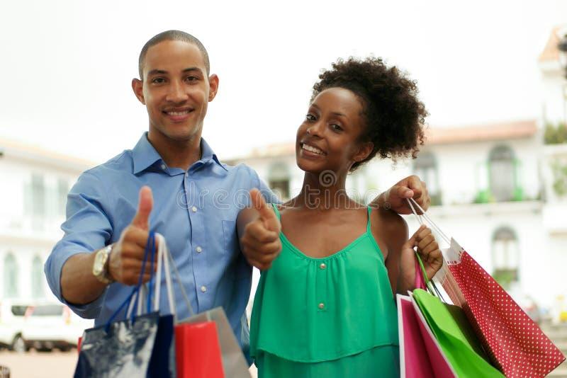 Shopping för ståendeafrikansk amerikanpar som ler med tummen upp royaltyfri foto