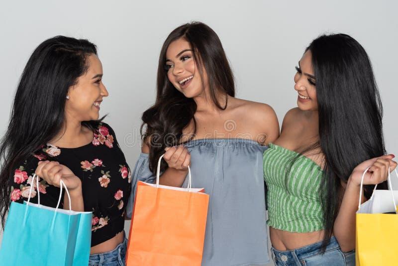 Shopping för tre latinamerikansk vänner arkivbilder