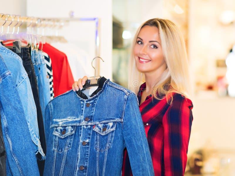 Shopping för ung kvinna i modelagret arkivfoton