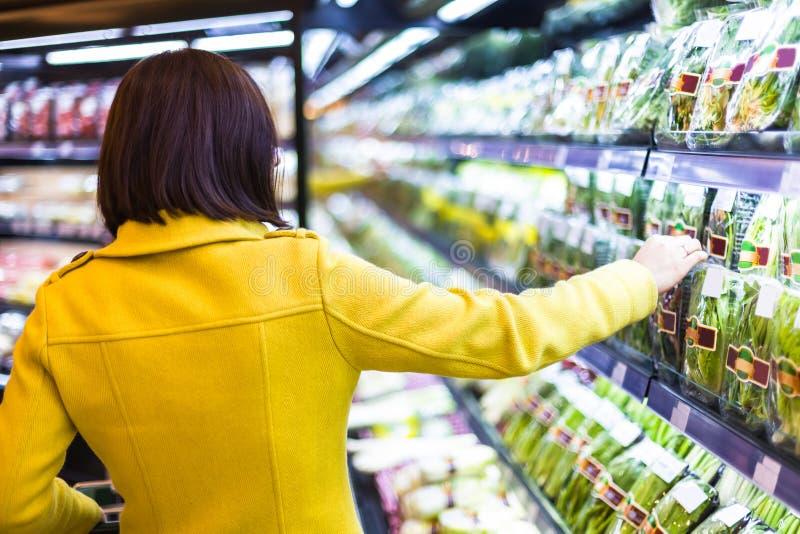 Shopping för ung kvinna i supermarket arkivfoton