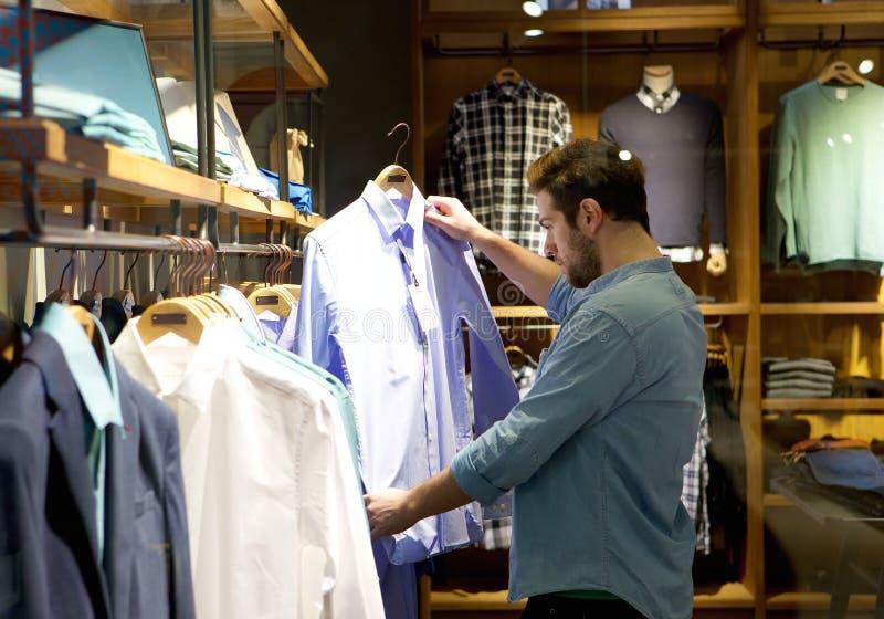 Shopping för ung man för kläder på lagret arkivfoto