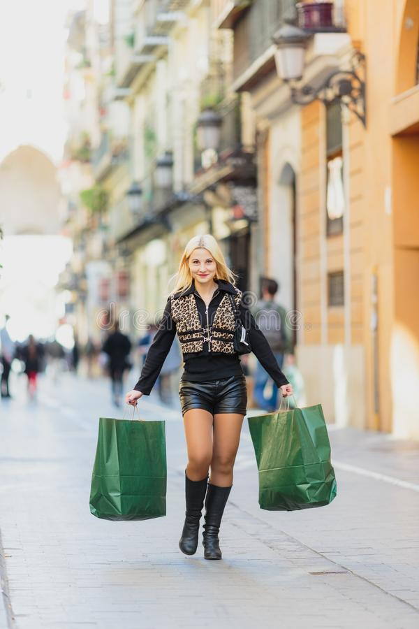 Shopping försäljning Härlig ung blond flicka med två dokument med olika förslagpackar arkivfoton