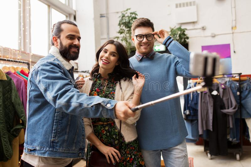 Friends taking selfie at vintage clothing store. Shopping, fashion and people concept - happy smiling friends taking picture by selfie stick at vintage clothing stock photos