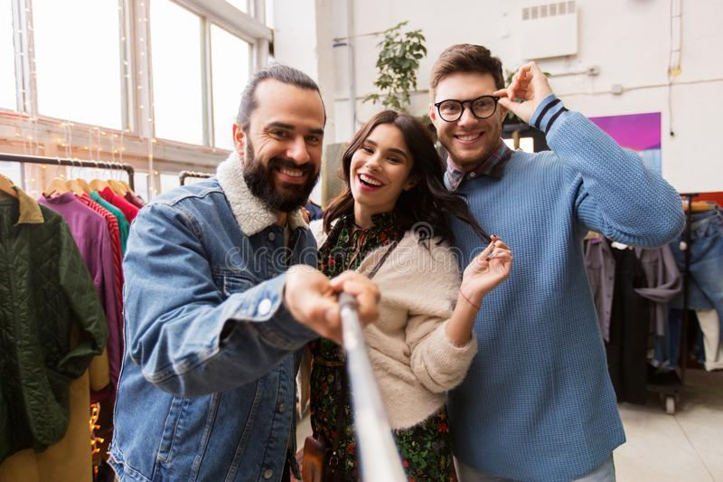 Friends taking selfie at vintage clothing store. Shopping, fashion and people concept - happy smiling friends taking picture by selfie stick at vintage clothing stock images