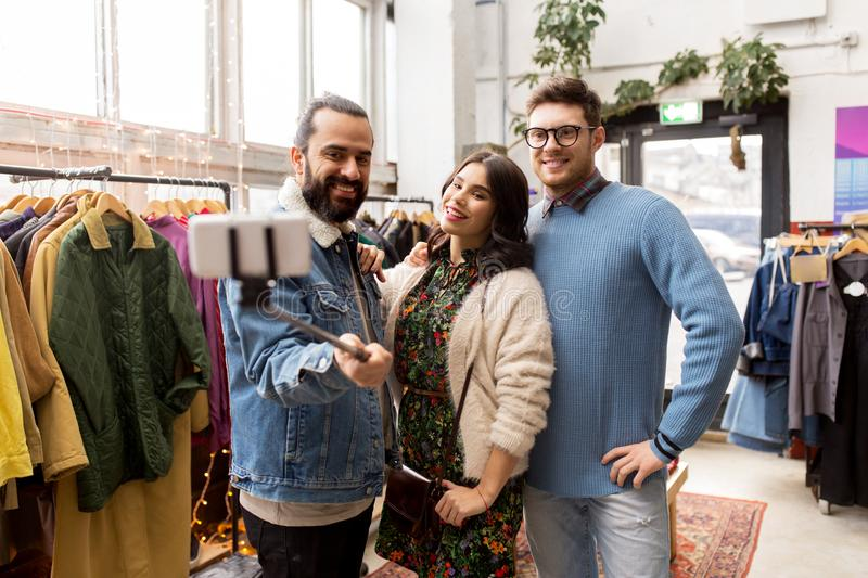 Friends taking selfie at vintage clothing store. Shopping, fashion and people concept - happy smiling friends taking picture by selfie stick at vintage clothing stock photo