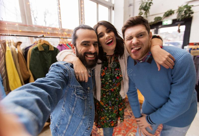 Friends taking selfie at vintage clothing store. Shopping, fashion and people concept - happy smiling friends taking selfie at vintage clothing store royalty free stock photography