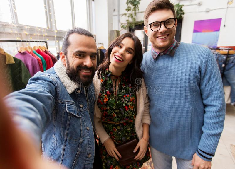 Friends taking selfie at vintage clothing store. Shopping, fashion and people concept - happy smiling friends taking selfie at vintage clothing store royalty free stock photo