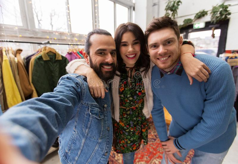 Friends taking selfie at vintage clothing store. Shopping, fashion and people concept - happy smiling friends taking selfie at vintage clothing store stock photography