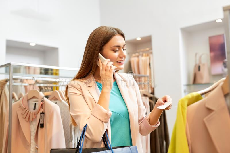 Woman calling on smartphone at clothing store. Shopping, fashion, sale and people concept - happy young woman choosing clothes and calling on smartphone in mall royalty free stock images