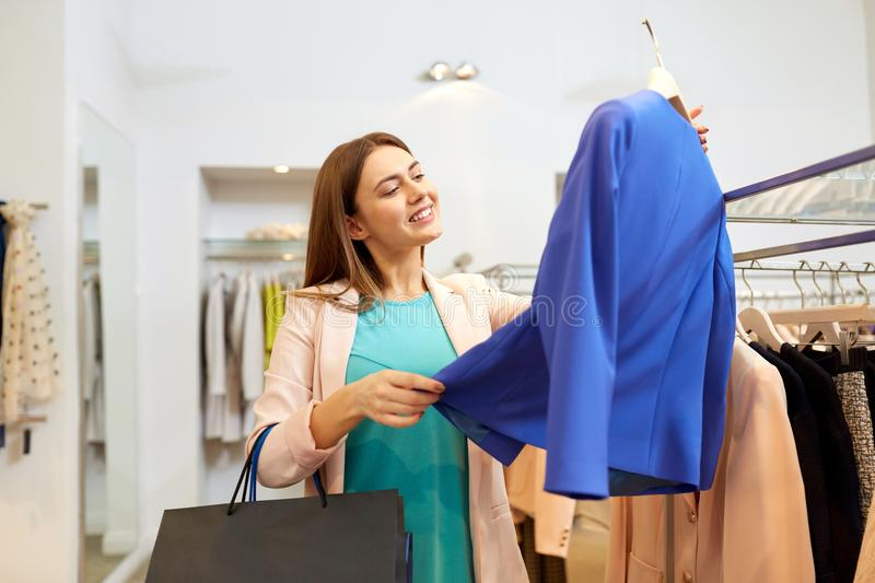 Happy woman choosing clothes at clothing store. Shopping, fashion, sale and people concept - happy young woman choosing clothes in mall or clothing store stock images