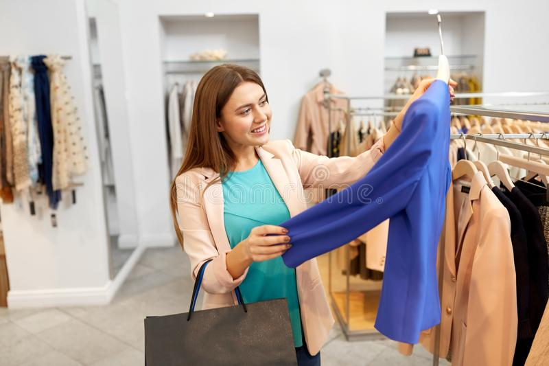 Happy woman choosing clothes at clothing store. Shopping, fashion, sale and people concept - happy young woman choosing clothes in mall or clothing store stock photography