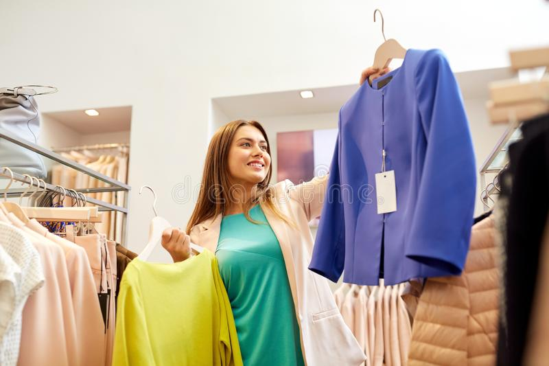 Happy woman choosing clothes at clothing store. Shopping, fashion, sale and people concept - happy young woman choosing clothes in mall or clothing store royalty free stock photography