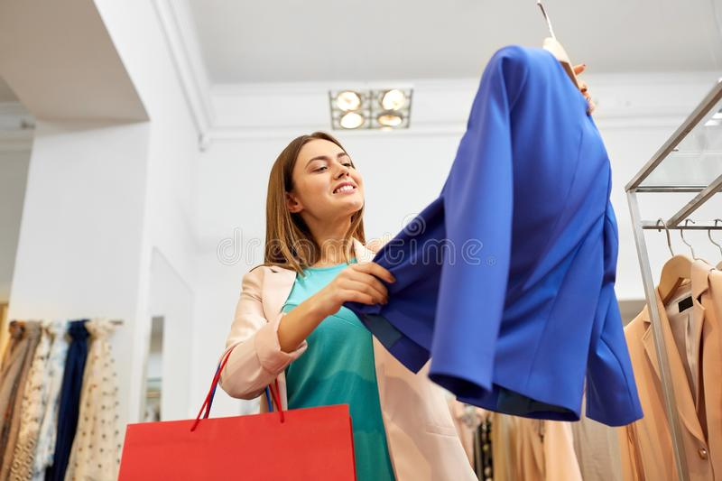 Happy woman choosing clothes at clothing store. Shopping, fashion, sale and people concept - happy young woman choosing clothes in mall or clothing store stock image