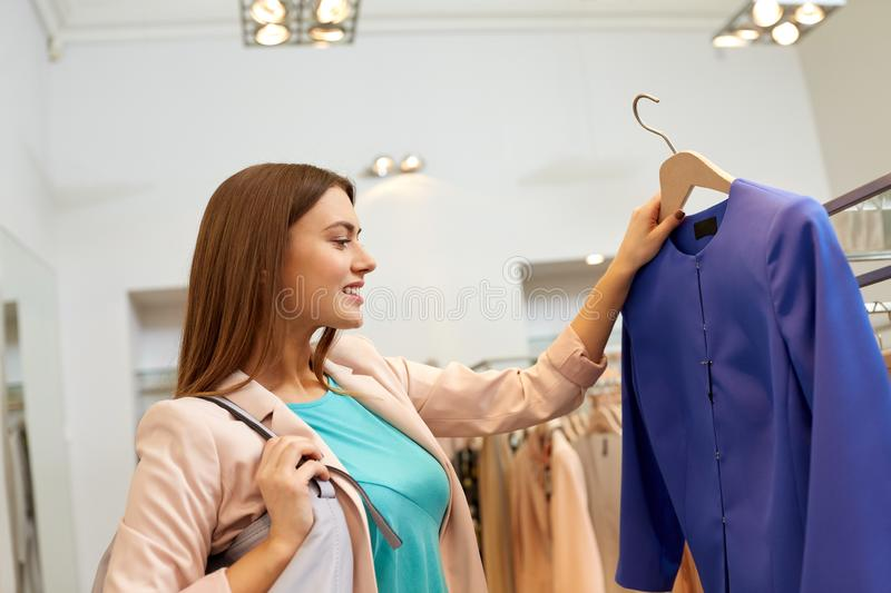 Happy woman choosing clothes at clothing store royalty free stock photography