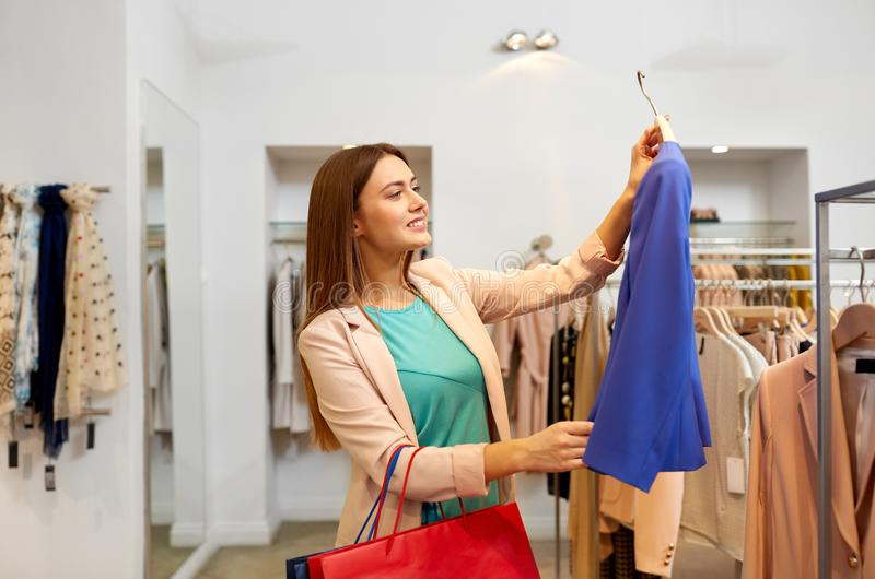 Happy woman choosing clothes at clothing store. Shopping, fashion, sale and people concept - happy young woman choosing clothes in mall or clothing store royalty free stock photo