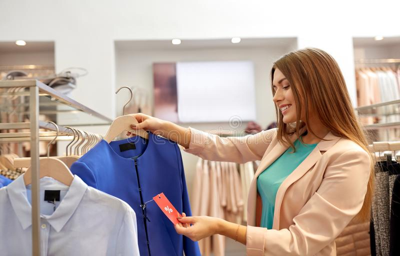 Happy woman choosing clothes at clothing store. Shopping, fashion, sale and people concept - happy young woman choosing clothes in mall or clothing store and royalty free stock photo