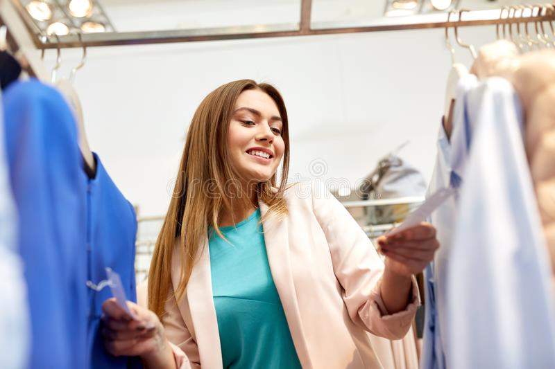 Happy woman choosing clothes at clothing store. Shopping, fashion, sale and people concept - happy young woman choosing clothes in mall or clothing store and royalty free stock images