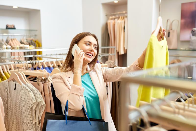 Woman calling on smartphone at clothing store. Shopping, fashion, sale and people concept - happy young woman choosing dress and calling on smartphone in mall or royalty free stock photography