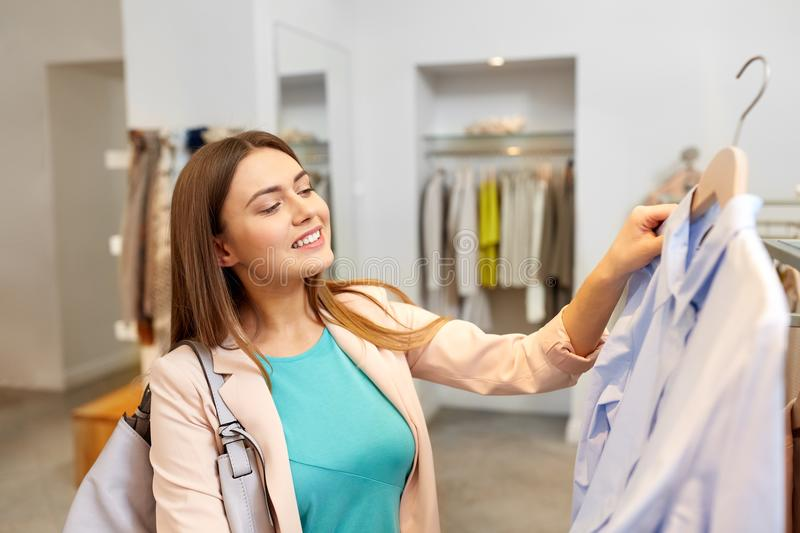 Happy woman choosing clothes at clothing store. Shopping, fashion, sale and people concept - happy young woman choosing shirt in mall or clothing store royalty free stock photography