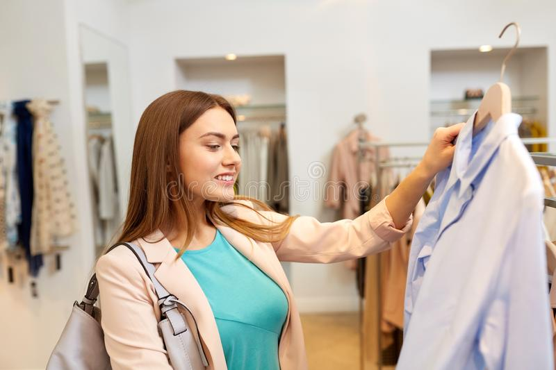 Happy woman choosing clothes at clothing store. Shopping, fashion, sale and people concept - happy young woman choosing shirt in mall or clothing store stock photos