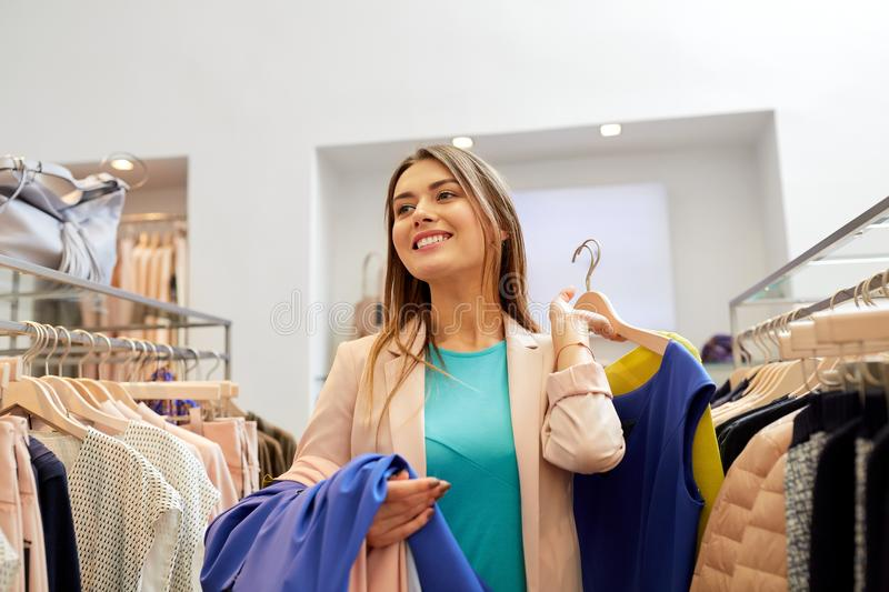 Happy young woman choosing clothes in mall. Shopping, fashion, sale and people concept - happy young woman with clothes on hangers in mall or clothing store stock photography
