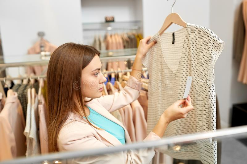 Woman choosing clothes at clothing store. Shopping, fashion, sale and people concept - young woman choosing clothes in mall or clothing store and looking at top stock image