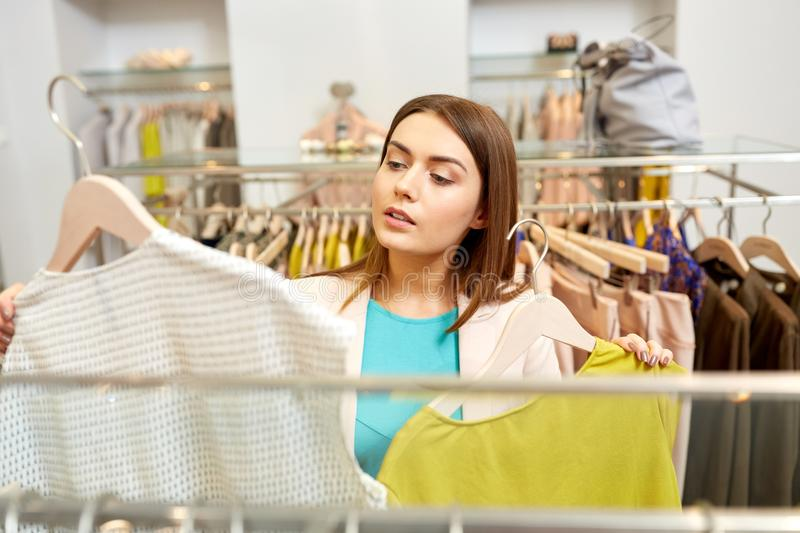Woman choosing clothes at clothing store. Shopping, fashion, sale and people concept - young woman choosing clothes in mall or clothing store royalty free stock photo