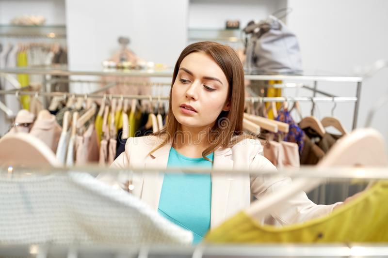 Woman choosing clothes at clothing store. Shopping, fashion, sale and people concept - young woman choosing clothes in mall or clothing store stock images