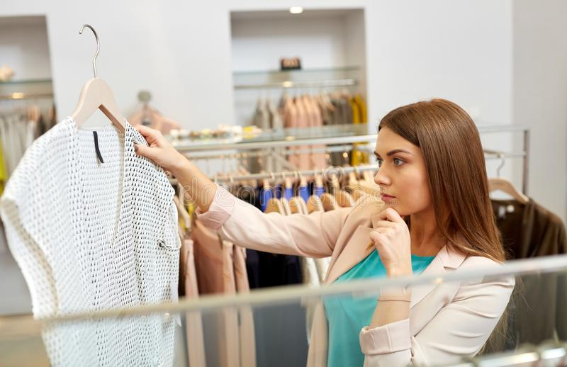 Woman choosing clothes at clothing store. Shopping, fashion, sale and people concept - young woman choosing shirt in mall or clothing store stock photo