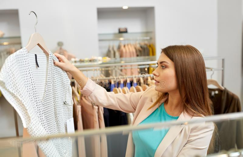 Woman choosing clothes at clothing store. Shopping, fashion, sale and people concept - young woman choosing shirt in mall or clothing store royalty free stock image