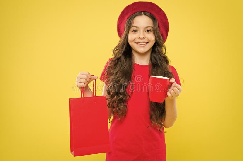 Shopping in france. parisian child on yellow. hairdresser salon. happy girl with long curly hair in beret hold shopping. Bag. beauty and fashion. little girl in stock photography