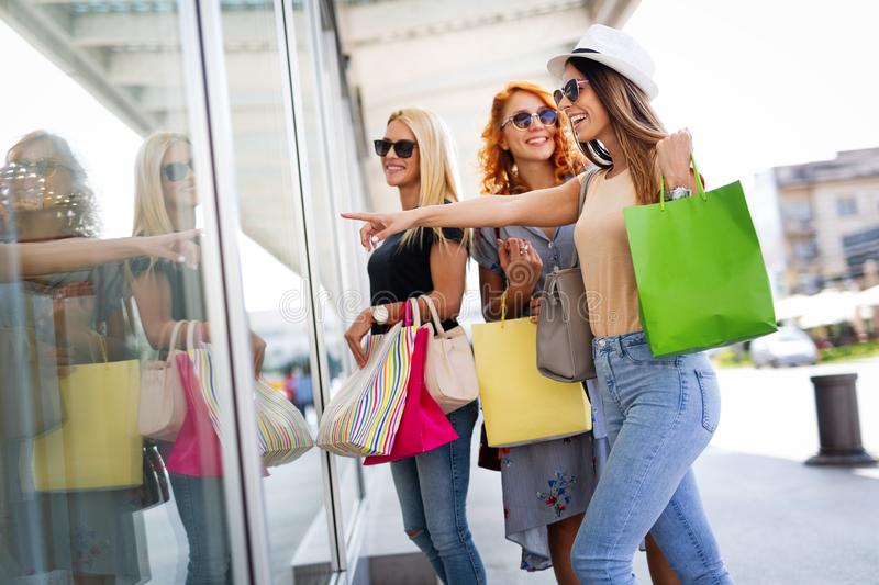 Shopping, fun and tourism concept. Beautiful girls with shopping bags in ctiy royalty free stock images