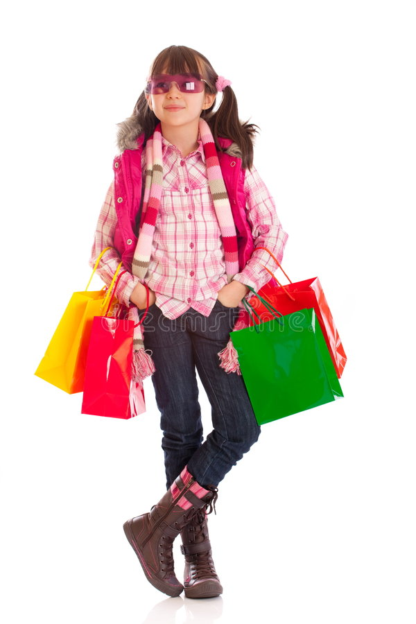 Shopping Girl. A girl wearing sunglasses carrying colorful shopping bags, isolated on a white background stock photos