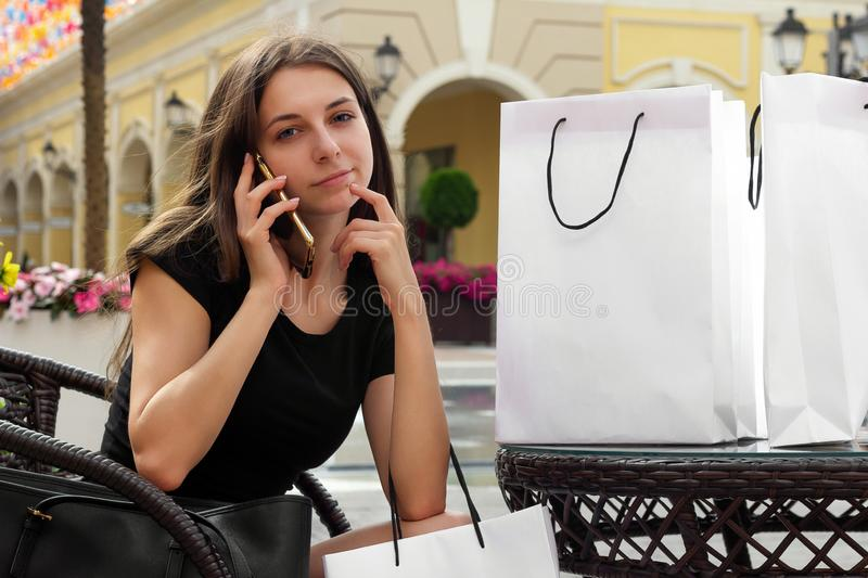 Shopping  girl talks to friends on the phone after shops. Choice stock photography