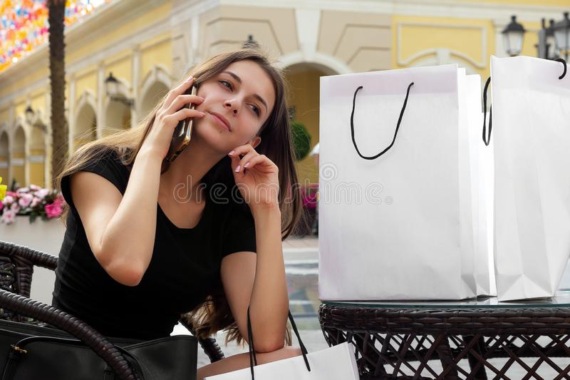 Shopping  girl talks to friends on the phone after shops. Choice royalty free stock photo
