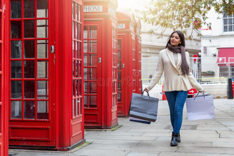 Shopping girl walks along red telephone booths in London, UK. Elegant, attractive urban city shopping girl walks along red telephone booths in London, UK, on her stock image