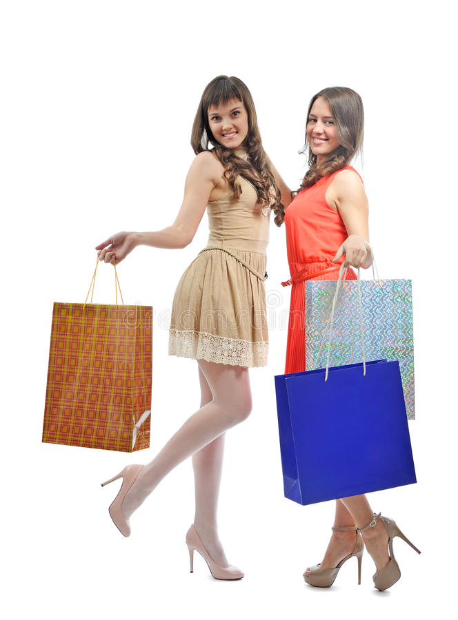 Shopping girls. Two attractive girls with shopping bags isolated on white background royalty free stock image