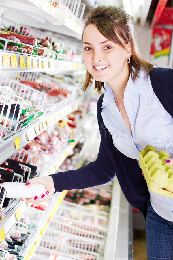 Shopping in grocery store. Smiling young woman shopping in a grocery store holding products royalty free stock photo