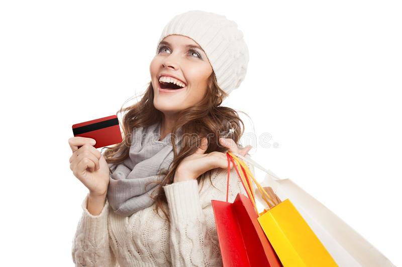 Shopping happy woman holding bags and credit card. Winter sales. Isolated stock photo