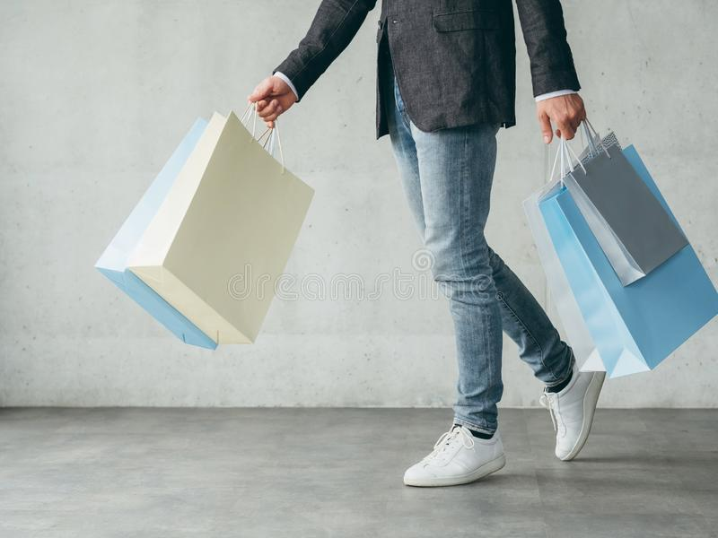 Shopping hobby man fashionist walking holding bags. Shopping hobby. cheery man fashionist walking and holding multiple bags with new outfits stock photography