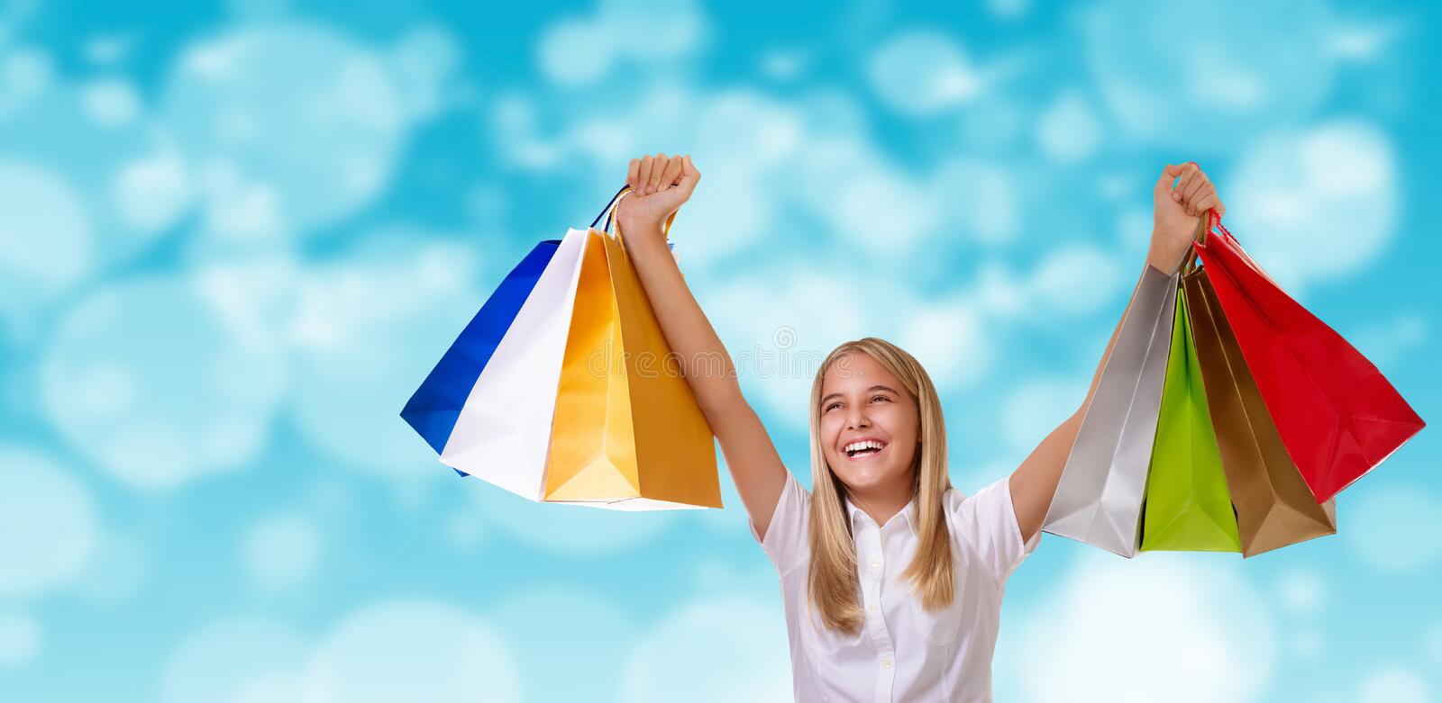 Shopping,holiday and tourism concept - happy cheerful girl with shopping bags over blurred background stock photos