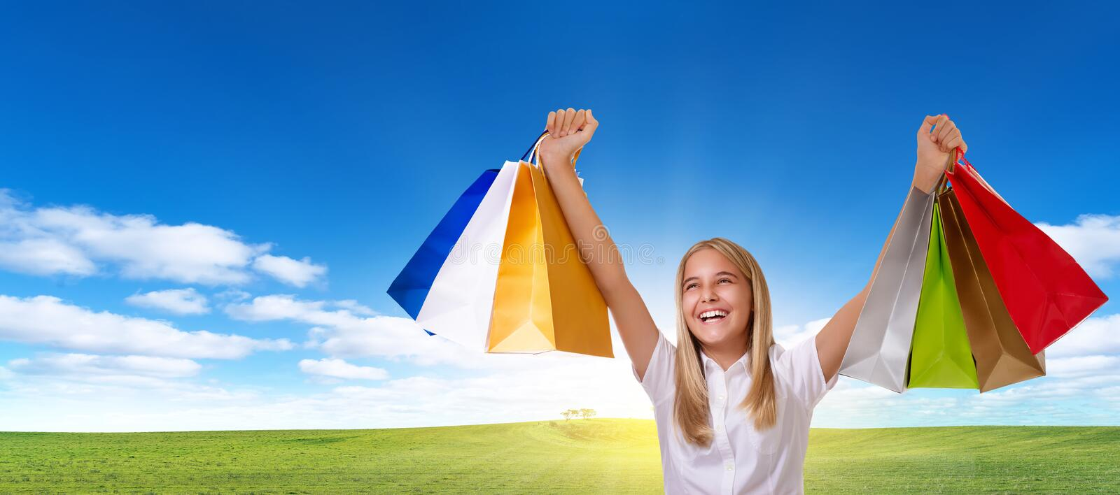 Shopping,holiday,tourism and people concept - young cheerful girl with shopping bags with copyspace royalty free stock photo