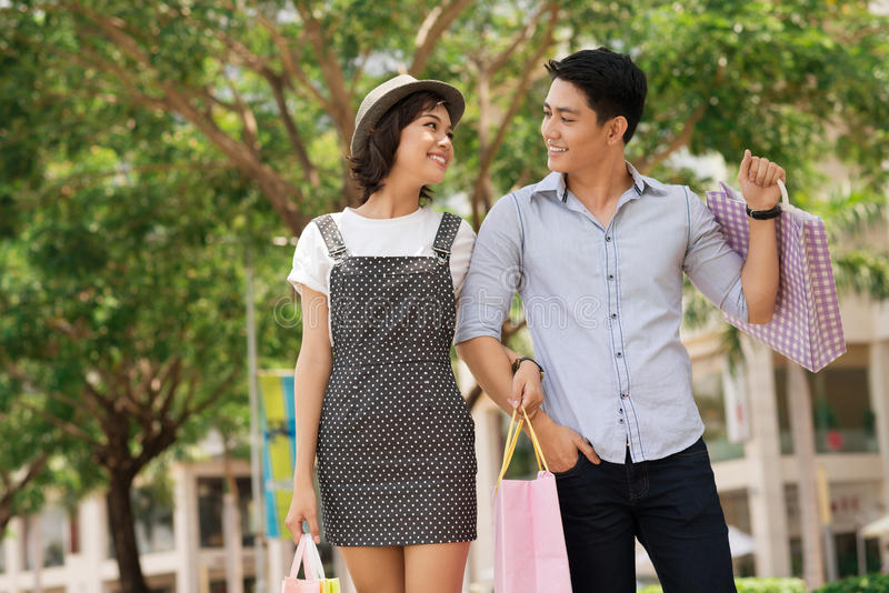 After shopping. Image of a young couple walking in the park after shopping stock image