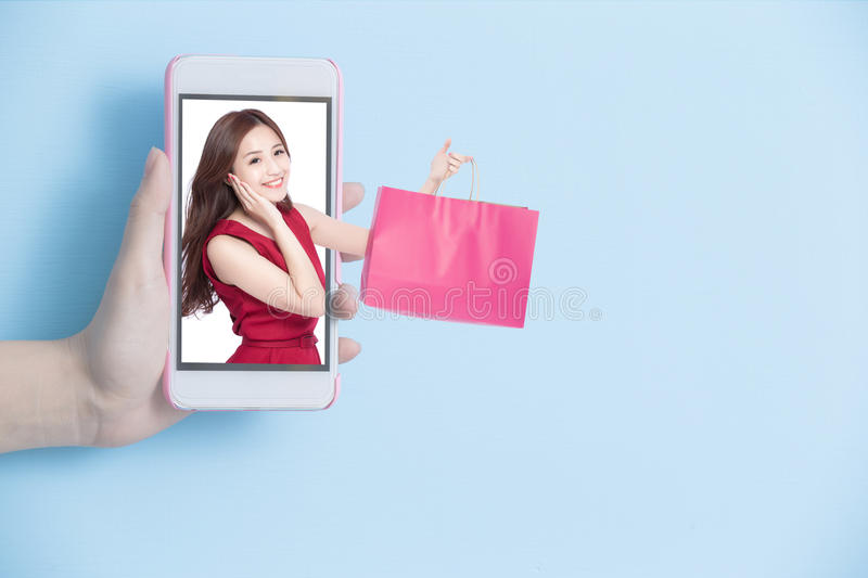 Shopping on internet concept. Hand take smart phone with woman hold shopping bag in screen on blue background stock photos