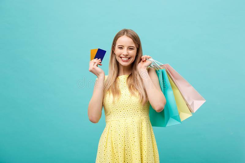 Shopping and Lifestyle Concept: Beautiful young girl with credit card and colorful shopping bags. Isolated on blue royalty free stock image