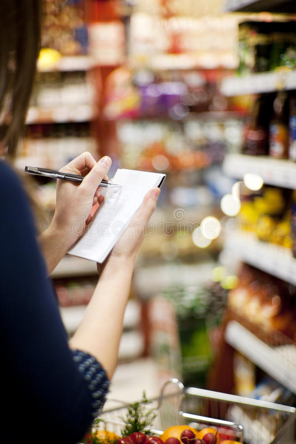 Shopping list. Supermarket: woman checking her shopping list stock image