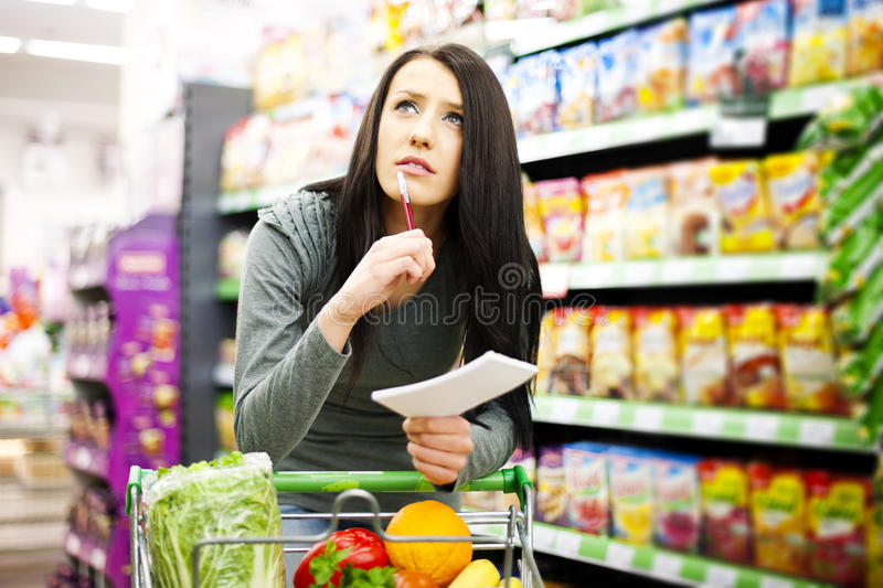 Shopping list. Supermarket collection: Woman checking her shopping list royalty free stock images